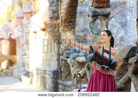 Beautiful young tourist with map standing near ancient castle