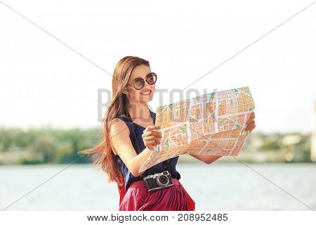 Beautiful young tourist with map standing on river bank