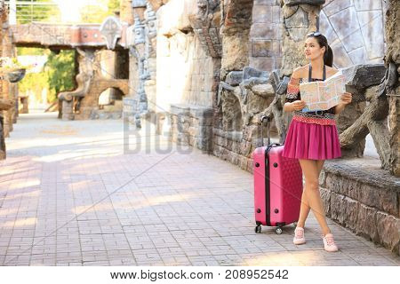 Beautiful young tourist with map and suitcase standing near ancient castle