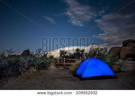 A campsite in the Mojave Desert shows a lighted blue tent as campers prepare to call it a night.