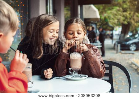Children having fun in outdoor cafe. Kids talking and drinking cocoa for the breakfast in the city street in autumn. Spending weekend with friends.