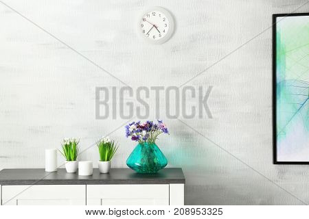 Lilac accent in modern interior. Vase with beautiful cornflowers on chest of drawers in living room