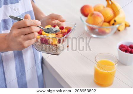Woman in pajamas eating oatmeal indoors