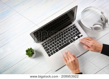 Woman using laptop on wooden background