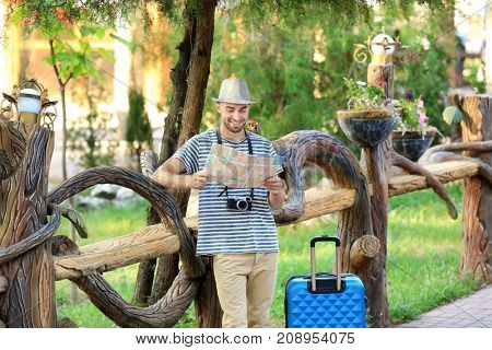 Handsome young tourist with map and suitcase standing near wooden fence in park