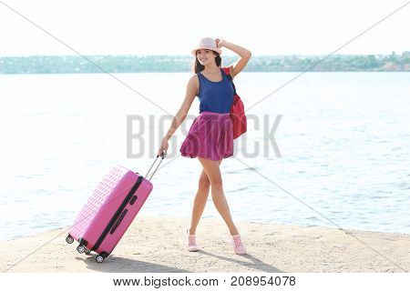 Beautiful young tourist with suitcase standing on river bank