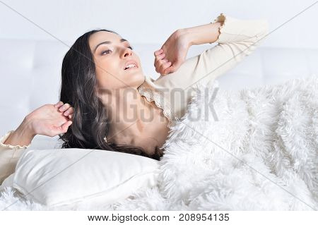 Beautiful Young Woman waking up  On Sofa At Home