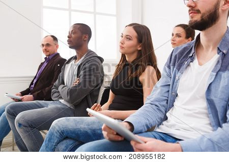 Group of people sitting at seminar, copy space. Serious and concentrated audience listening to speaker. Education, conference, workshop concept