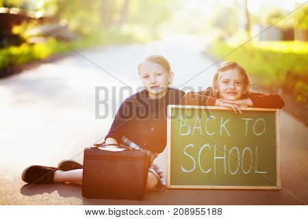Adorable old-fashioned little 6 years old and 10 years old girls wearing school uniform. Smiling holding school bags and back to school chalkboard sitting on a road waiting for a school bus. Preschooler and schoolgirl sisters schoolkids are happy back to
