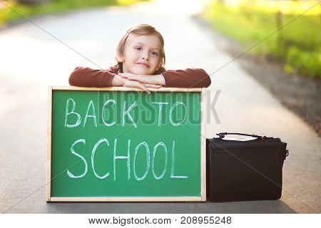 Cute preschool girl ready for her first year at school wearing school uniform holding school bag and back to school chalkboard.