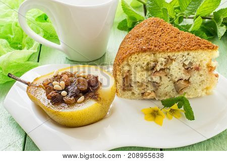 Sweet dessert: baked pear with raisins dates honey nuts spices and slice of delicious pie with apples on white plate mug with tea and mint on green wooden table with green gauze napkin