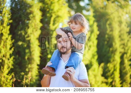 Little girl riding on dads neck. Fatherhood caring single father family relationships and friendship. Toddler girl loving her daddy. Summer day blue sky.