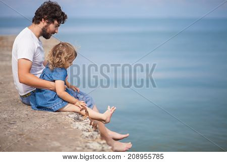 Handsome young father and his little daughter together at the beach sitting on walkway looking sea and sky. Family active leisure. Single father.