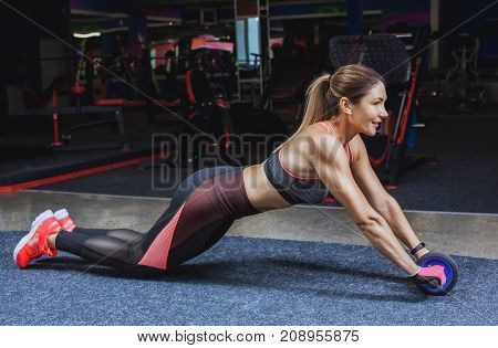 Slim bodybuilder girl does the exercises with Ab Wheel in the gym. Sports concept fat burning and a healthy lifestyle.