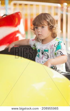 Toddler kid ride electric car attraction having fun at summer day lifestyle. Theme park for children.