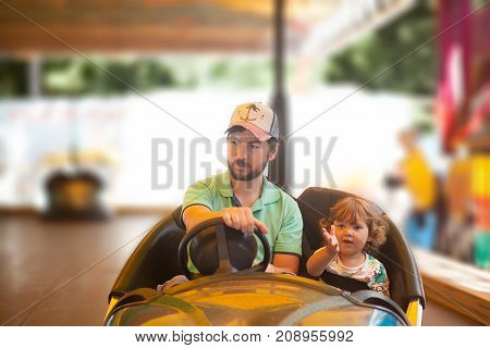 Father and his cute little daughter ride electric car together amusement theme park. Family lifestyle.