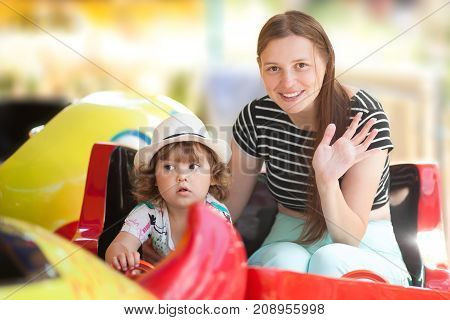 Toddler girl and her young mom together in the amusement park lifestyle. Riding children attraction sitting in the color wagon. Summer day.