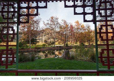 Looking through an elaborate gazebo window to a autumn landscape of falling leaves on changing trees next to a clam pond and green grass.