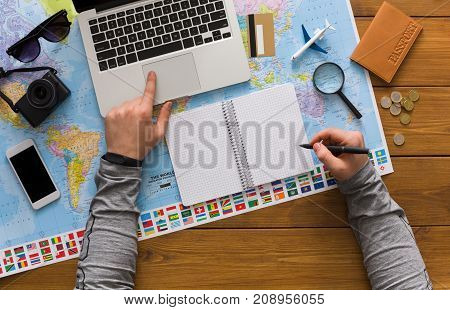 Travel planning concept top view. Taking notes to notebook on map background, search for best trip in laptop, copy space for text