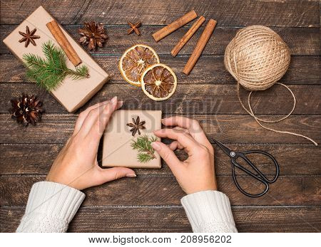 Woman decorating Christmas gifts. Presents wrapping inspirations. Hands gift boxes ball of jute cinnamon sticks anise orange slices fer tree branches and retro scissors on rustic wooden background.
