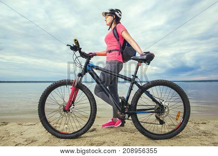 One young woman an athlete in pink shoes walks with a mountain bike in the morning on the river bank.