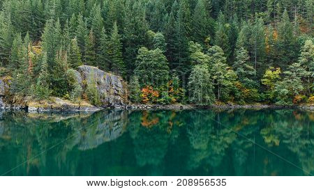 Green colored lake water with reflection of evergreen trees, autumn colors and rocks along the shoreline.