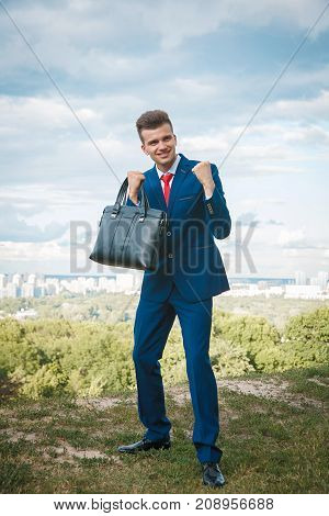 Cheerful smiling businessman who made a good deal dressed in blue suit and red tie with a briefcase in his hand against the backdrop of the city and the sky
