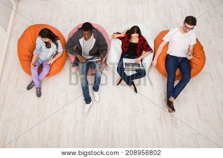 Group of young friends using gadgets sitting indoors at university campus and working together on creative task, top view