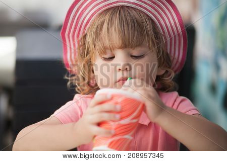 Adorable little girl drinking from glass with straw wearing straw hat summer vaccation.