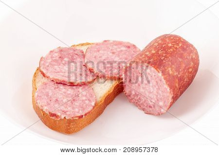 sandwich and a piece of sausage on a light plate looks appetizing