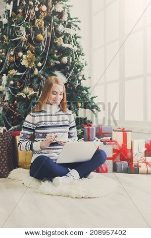 Happy girl gereeting friends with christmas in video chat on laptop. Young woman sitting under decorated pine tree among gift boxes and packages in home interior, having coffee, copy space on window