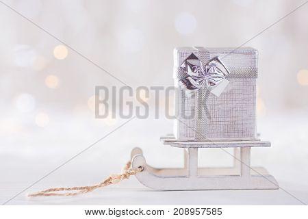 Little Pretty Gift Box On Toy White Sled On Light Bokeh Background