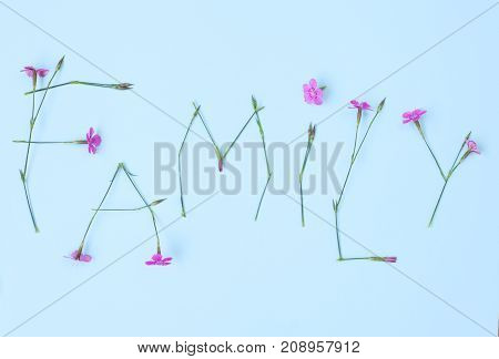 Word FAMILY made of flowers on light blue backgroung.