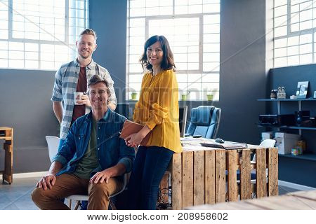 Portrait of three casually dressed young office coworkers smiling confidently while working together in a large modern office