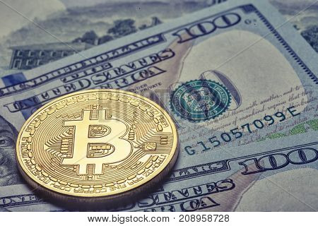 Golden shiny bitcoin on the background of one hundred dollar bills. The concept of virtual business and currency.