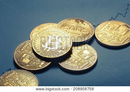 Virtual currency bitcoin lies on paper with a growing graph. The concept of virtual business and currency.