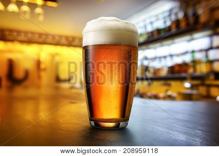 Glass of lager on a wooden table in pab