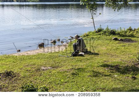 Belarus, Minsk - 10.07.2017: On the shore of the lake a man installed several fishing rods for fishing