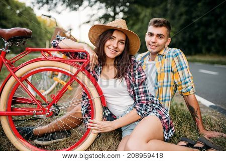 Love couple with vintage bikes sitting on roadside