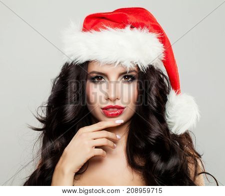 Perfect Christmas Woman in Santa Hat. Beautiful Brunette Fashion Model with Makeup and Long Healthy Wavy Hair