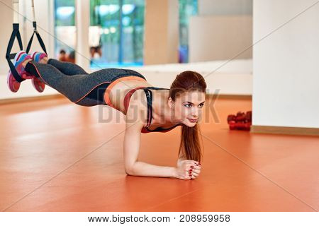 Fit girls in gym doing plank exercise for back spine with strap