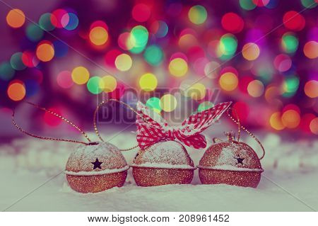 Greeting Christmas Card with Gold Jingle Bells on Colorful Bokeh Background. Image toned