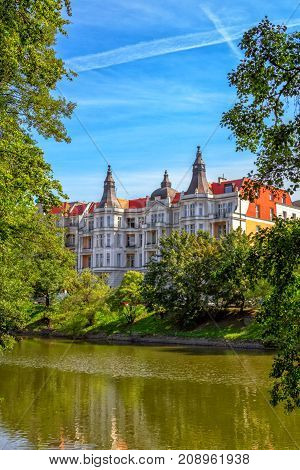 View of beautiful historic building on the river Odra bank in Wroclaw through green trees and branches over blue sky