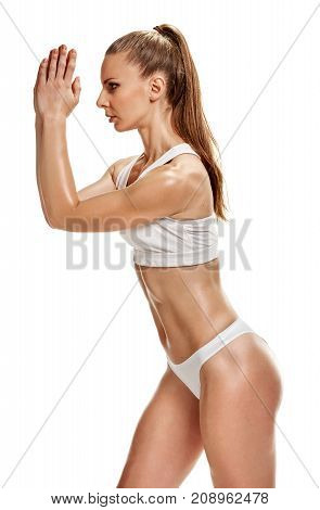 Young fit sportswoman in drawers doing exercises on white background