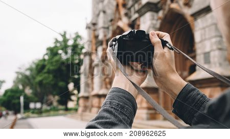 Another picture of a good blach camera device. It is in man's hands. The guy is holding it because ha want to take a picture of an old church. Close up