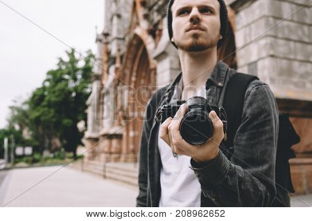 Attractive and serious tourist is staying outside near the brown building. He is looking straight forward with a serious sight and holding small black camera in his left hand. Close up. Cut view
