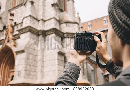 A picture of a guy shooting the old gothic church in a big city. He is holding a camera in his hands. He is waiting for a moment when the picture will show up on the camera's display. Close up. Cut view