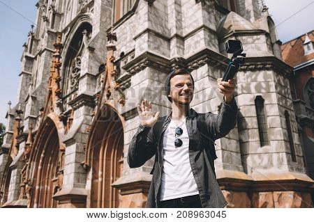 This nice picture is showing a guy that likes to travel al around the world. Now he is in a big city. The traveller decided to take a selfie and waving with his hand at the same time. The smile of this guy is awesome.