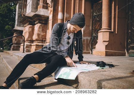 A picture of a tourist sitting on the steps near the brown collonies and looking down to the map. He is trying to find location and adress of place where he wants to go.