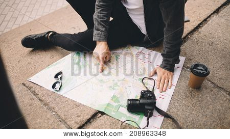 Close view of a young hipster that likes to travel. He decided to have some rest and sit down on the steps on the street. His coffee is getting colder while the guy is studing the map of the city. Close up. Cut view